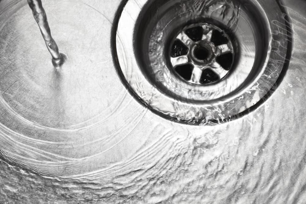シンクの蛇口から水を出して排水口に流れている