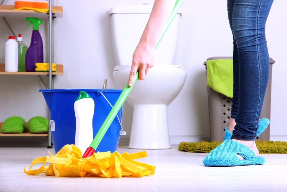 トイレの床にモップをかけている