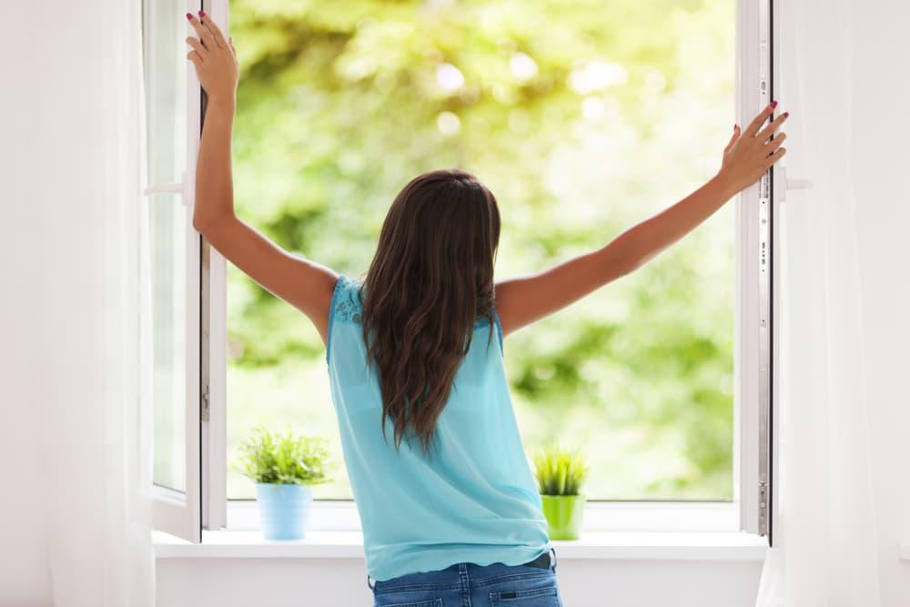 部屋の窓を開けてスッキリしている女性