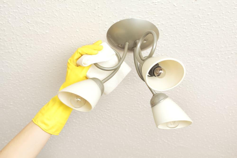 照明器具を拭いている手