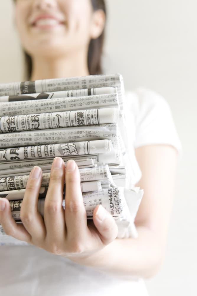 新聞紙を持っている女性