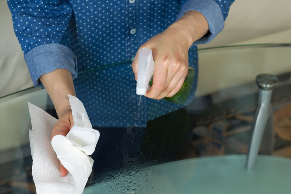 ガラステーブルの手垢を拭き取っている女性