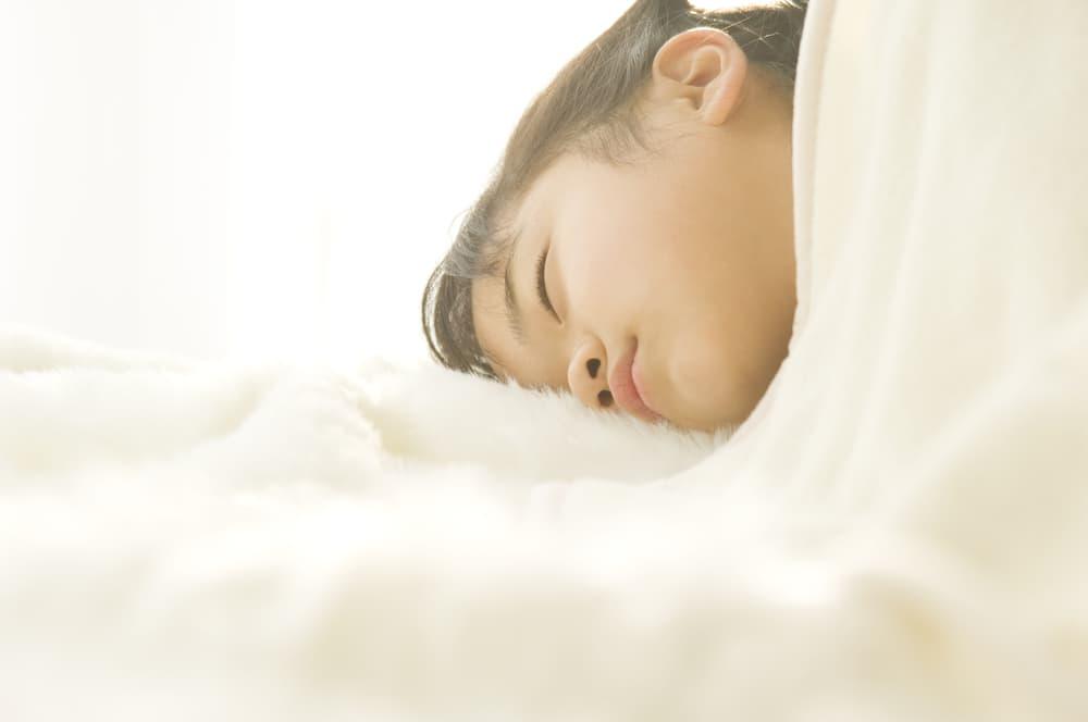 子供が布団で寝ている