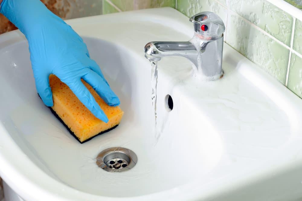 洗面所をスポンジで掃除している