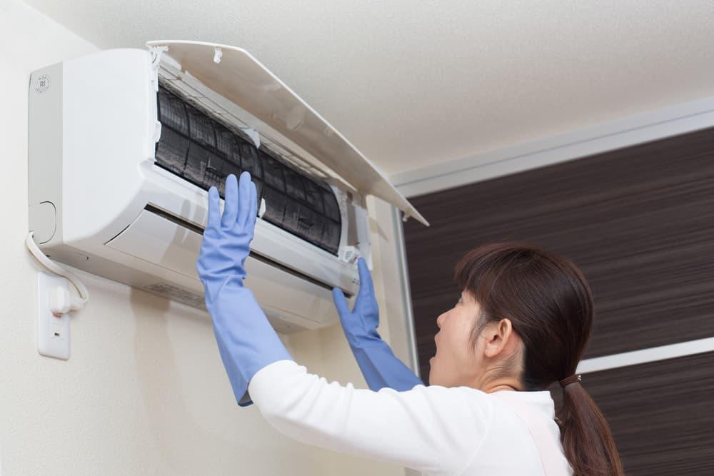 エアコン内部の汚れを見て驚く女性