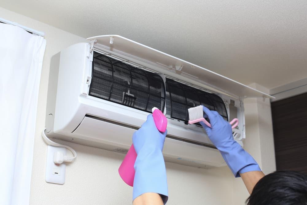エアコンフィルターを掃除している女性
