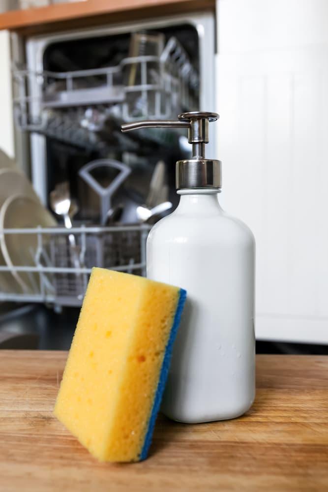 食器洗い機の前に置かれた洗剤とスポンジ