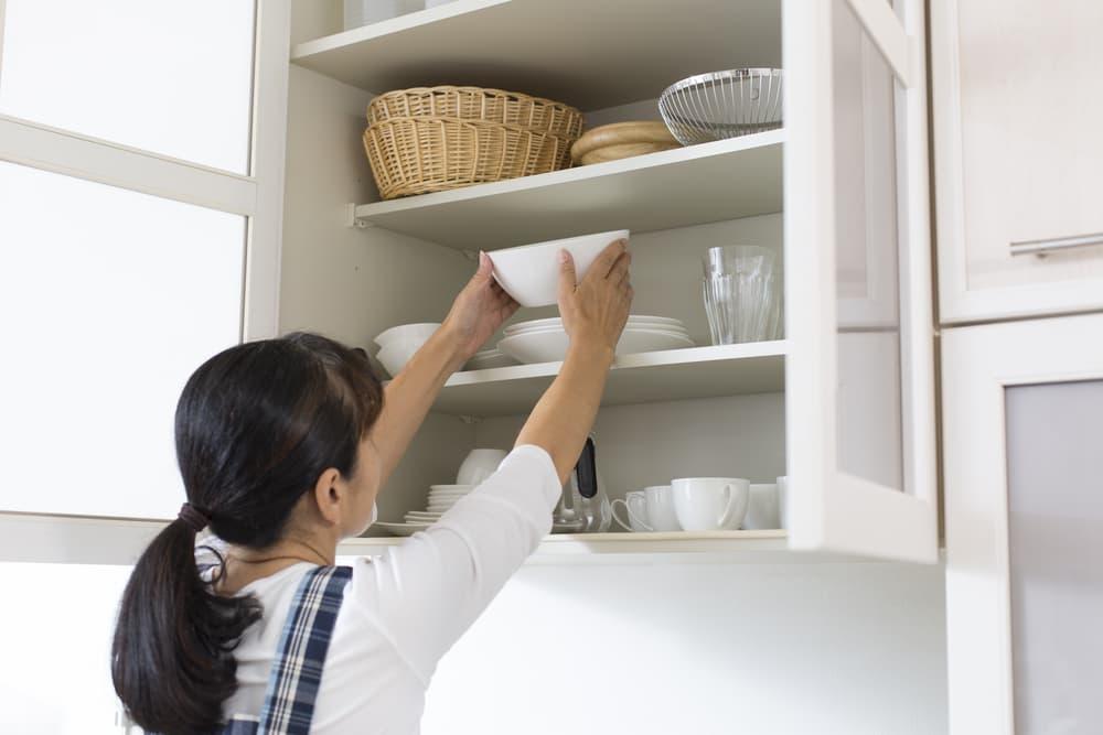棚の中から物を取り出している女性