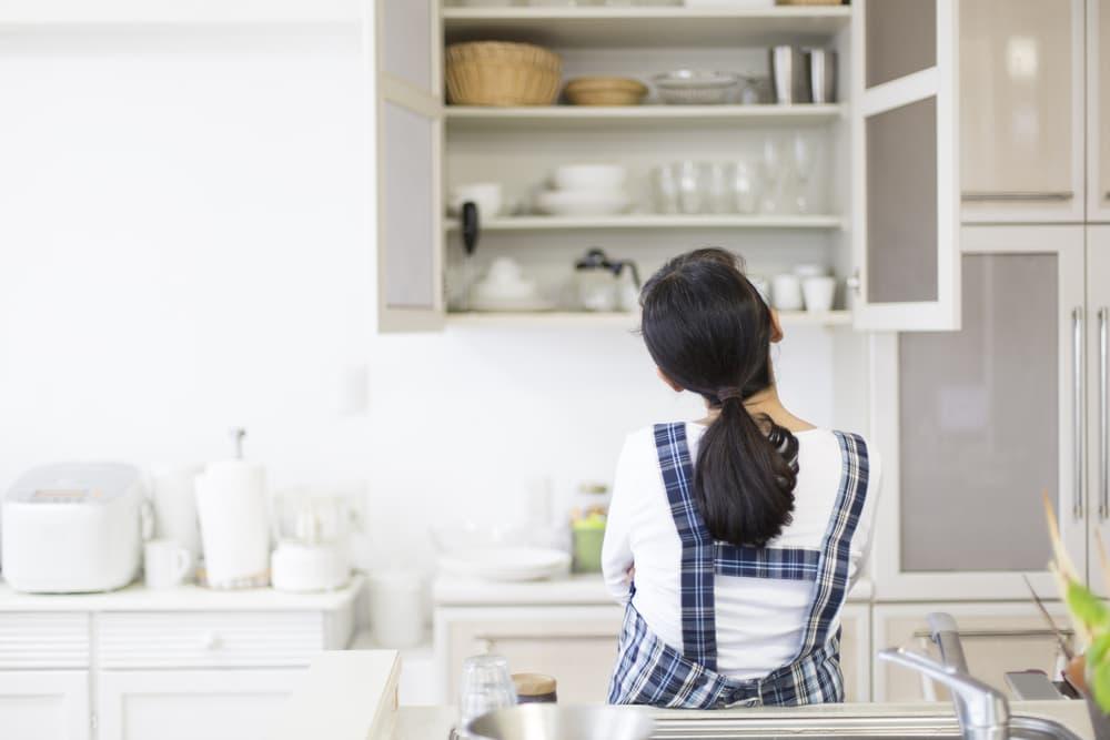 収納棚の戸を開けて考え込んでいる女性