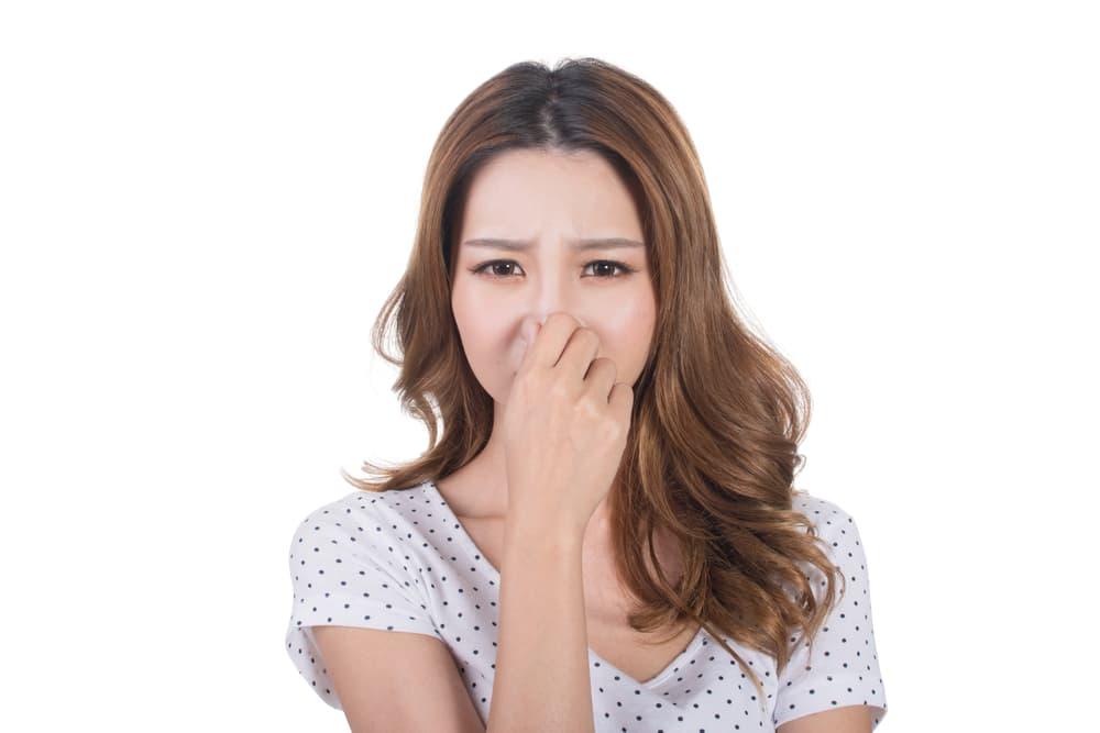 嫌な臭いに鼻をつまむ女性