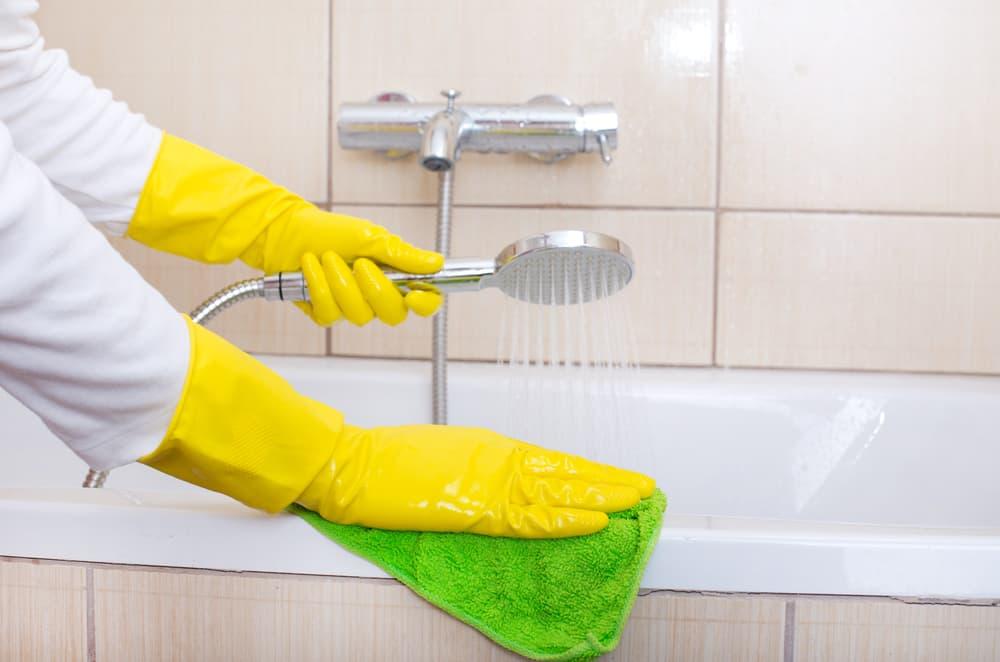 シャワーを流しながら浴室を掃除している