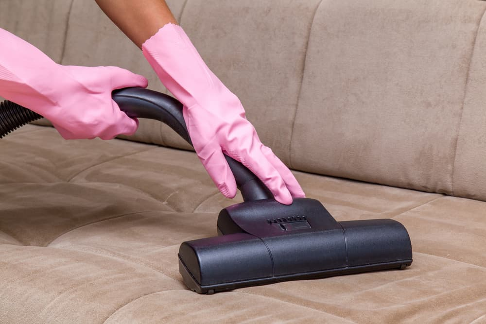 ゴム手袋をはめてソファに掃除機をかけている