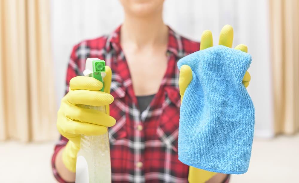 タオルとスプレーボトルを持っている女性