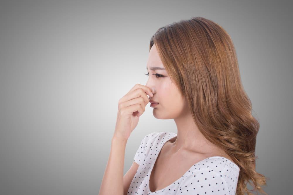 鼻を塞いで嫌な顔をしている日本人女性