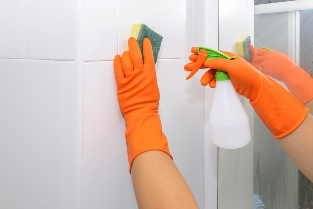 浴室の壁に洗剤をスプレーしている