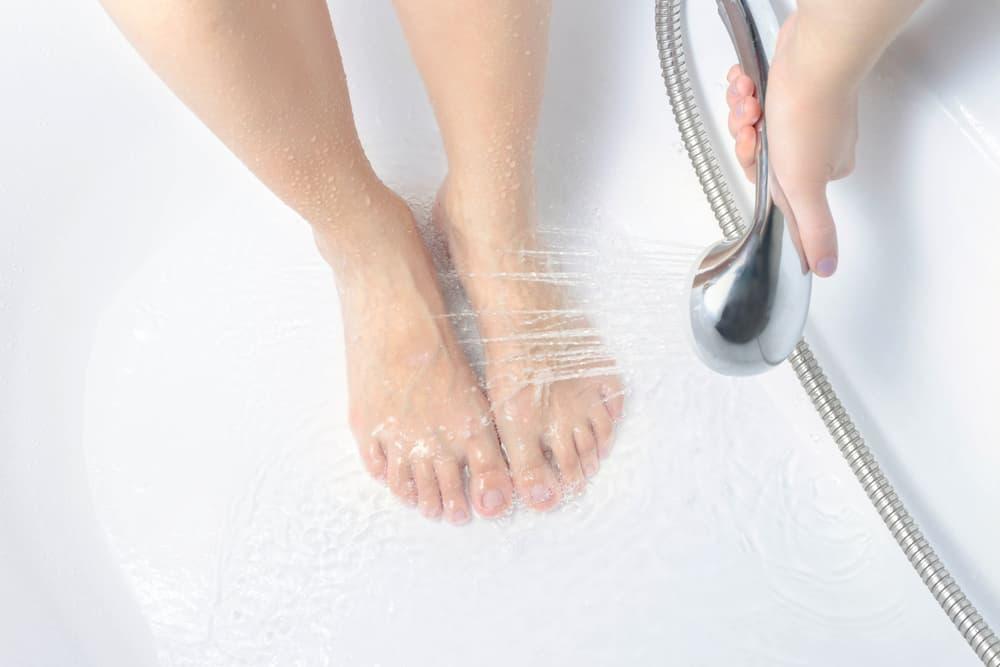 シャワーの水を足にかけている