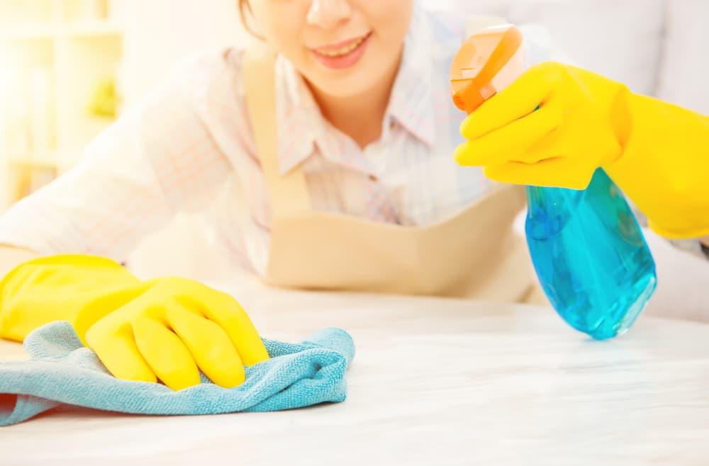 スプレーと布巾で拭き掃除をしている女性