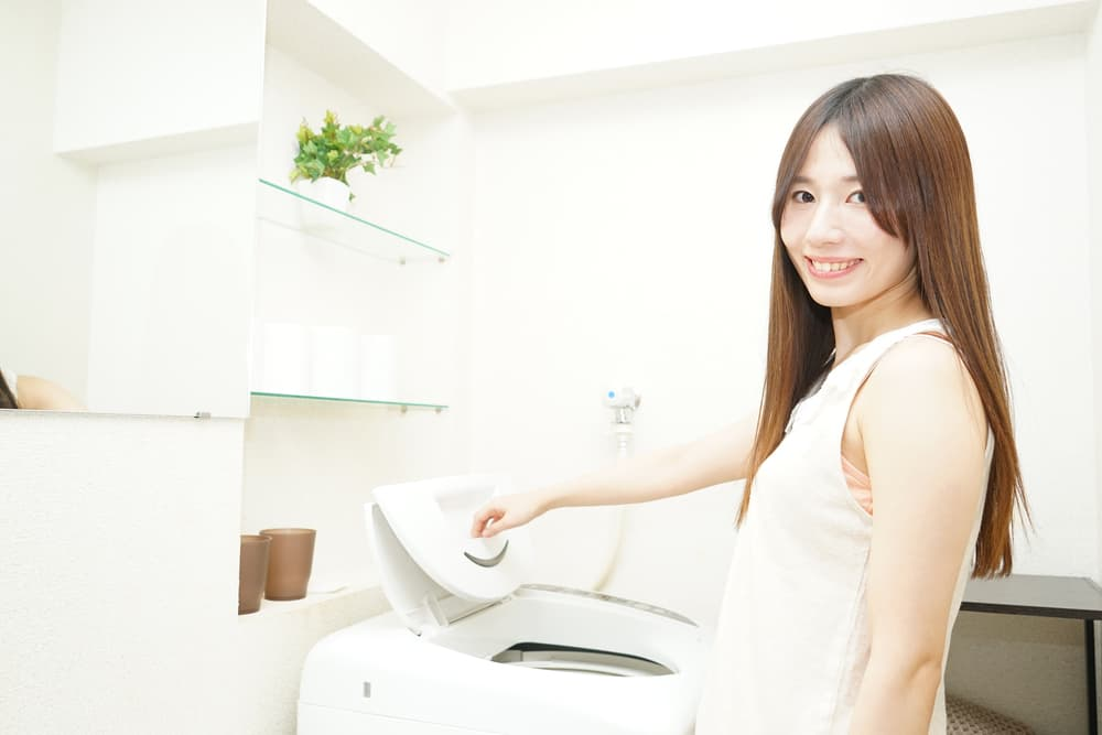 女性が洗濯機の蓋を開けている