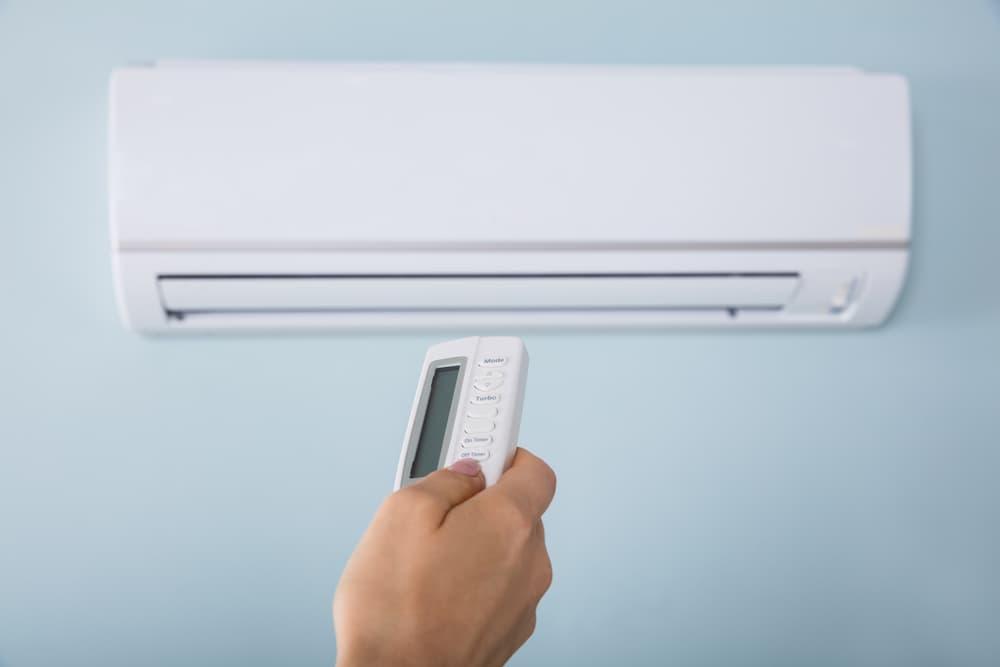 エアコンとリモコンを持つ手