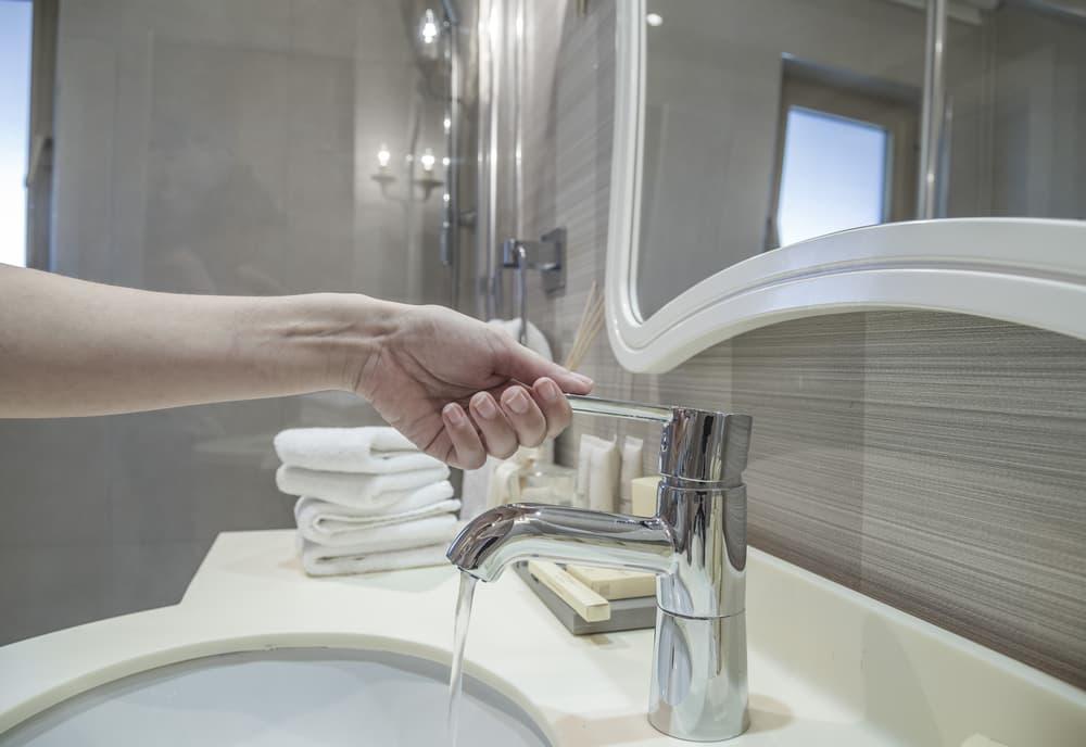 洗面所の蛇口をひねっている