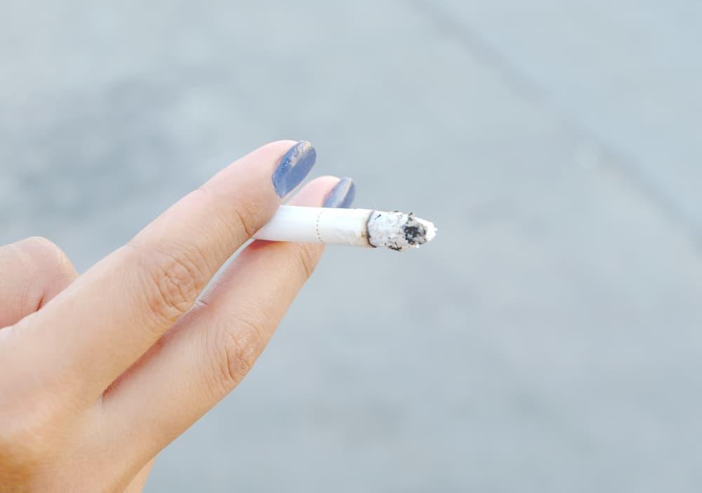 吸いかけのタバコを持っている