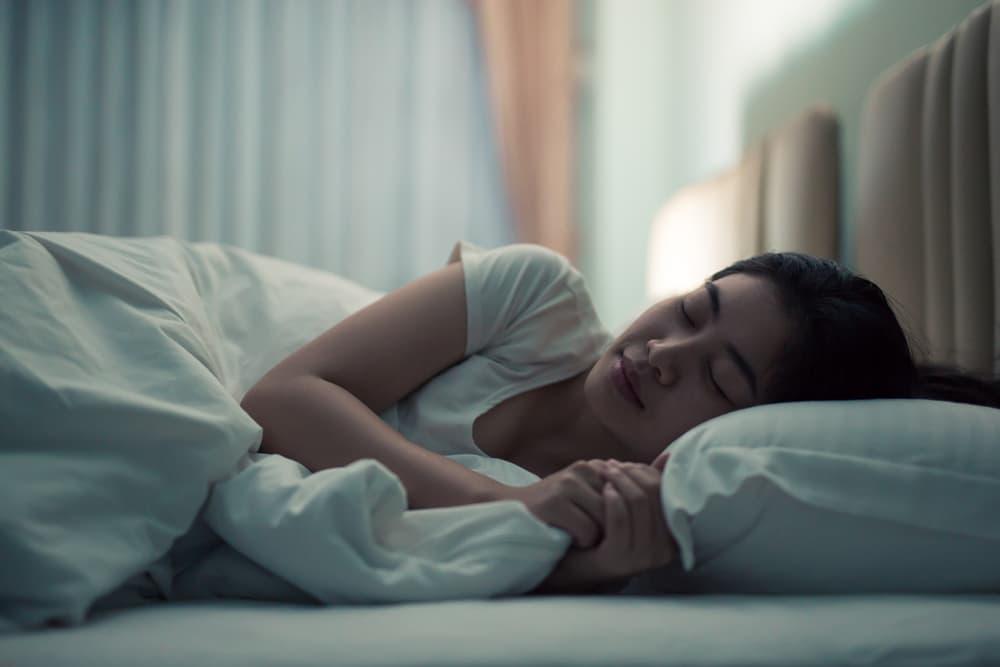ベッドで気持ちよさそうに寝ている女性