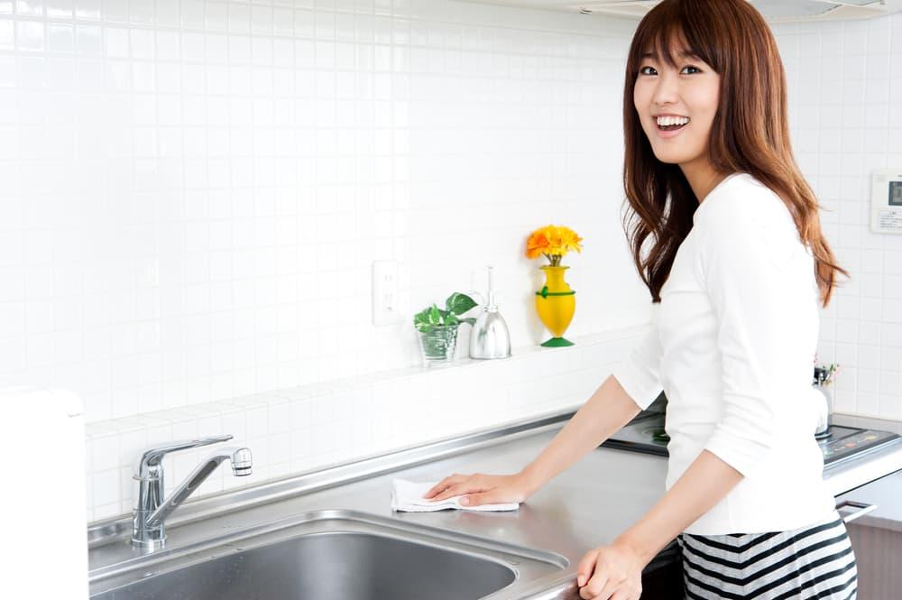 キッチンのシンク周りを拭いている女性