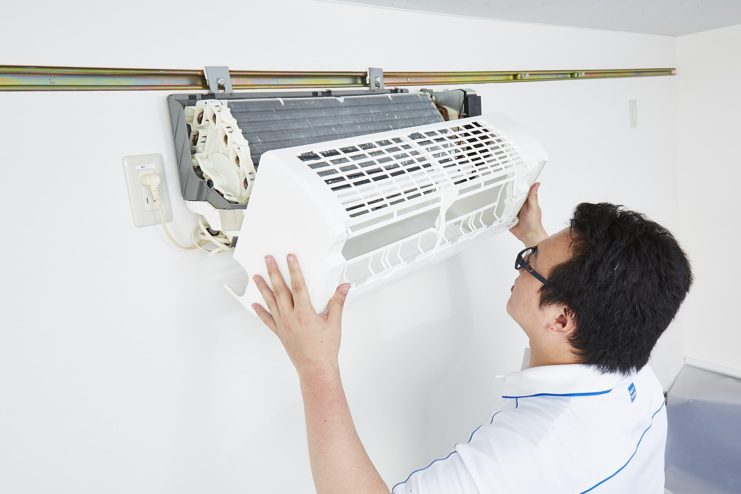 エアコンを分解しているプロ