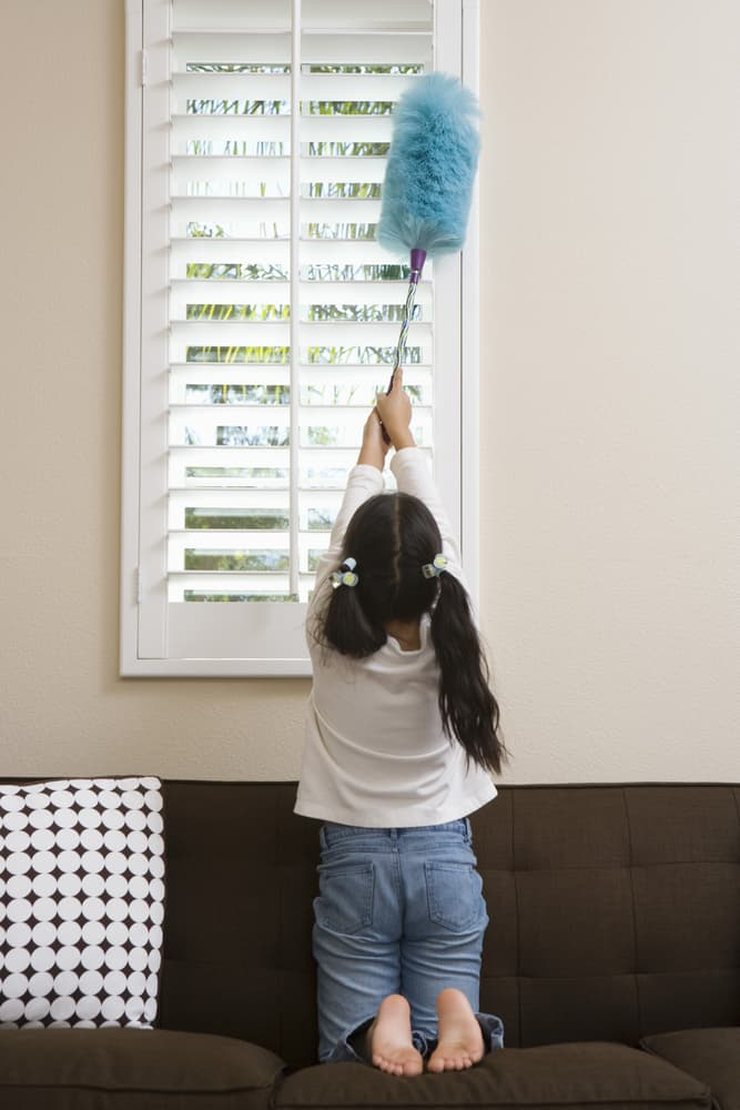 窓枠を掃除する少女