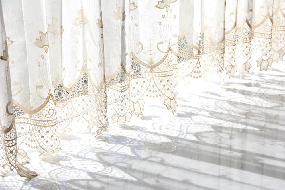 白を基調とした部屋にレースカーテンがかけてある