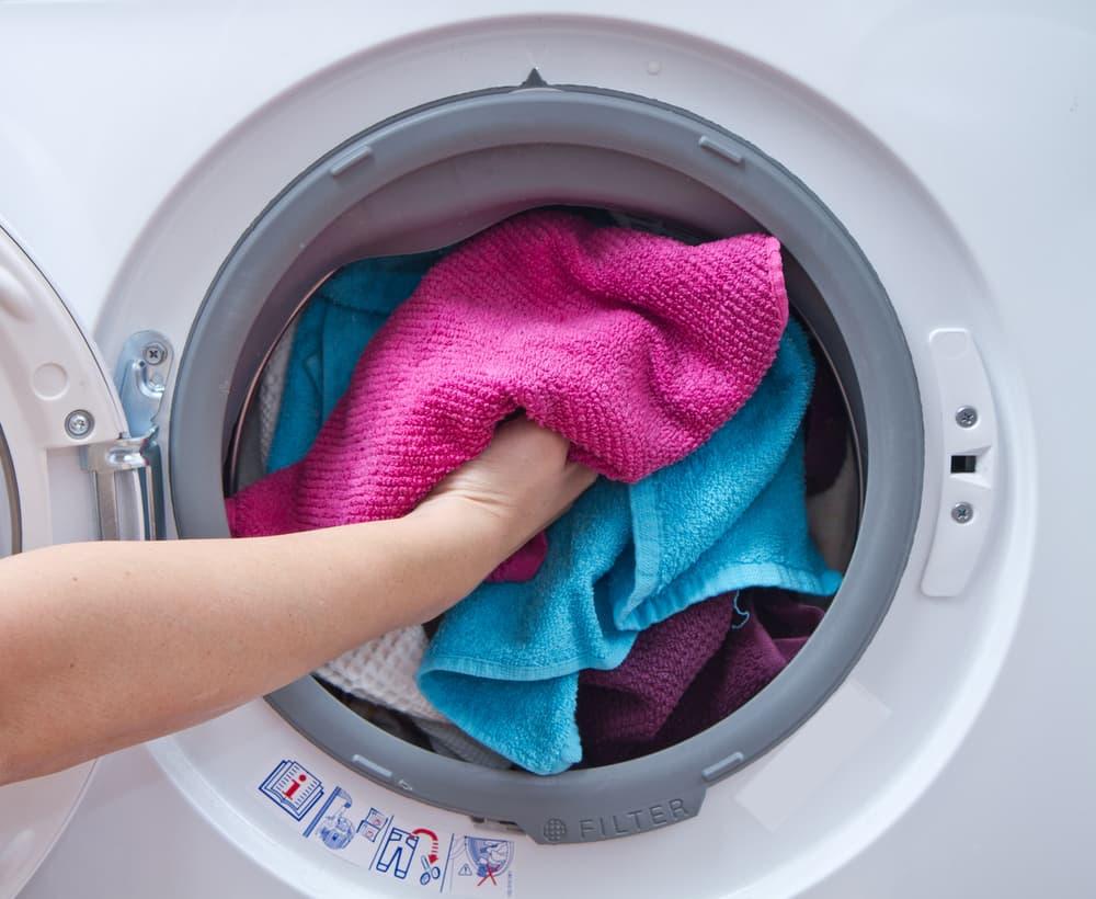 洗濯機に衣類を詰め込んでいる
