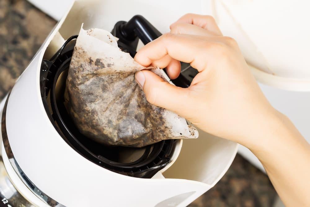 コーヒーのフィルターを取る女性の手元