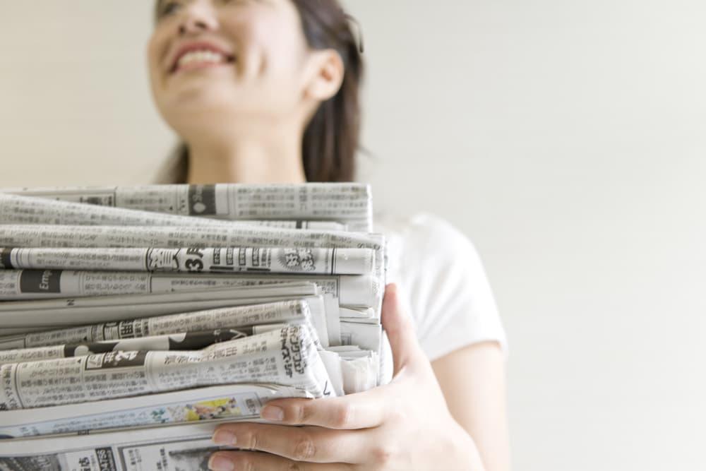 女性が新聞紙の束を持っている