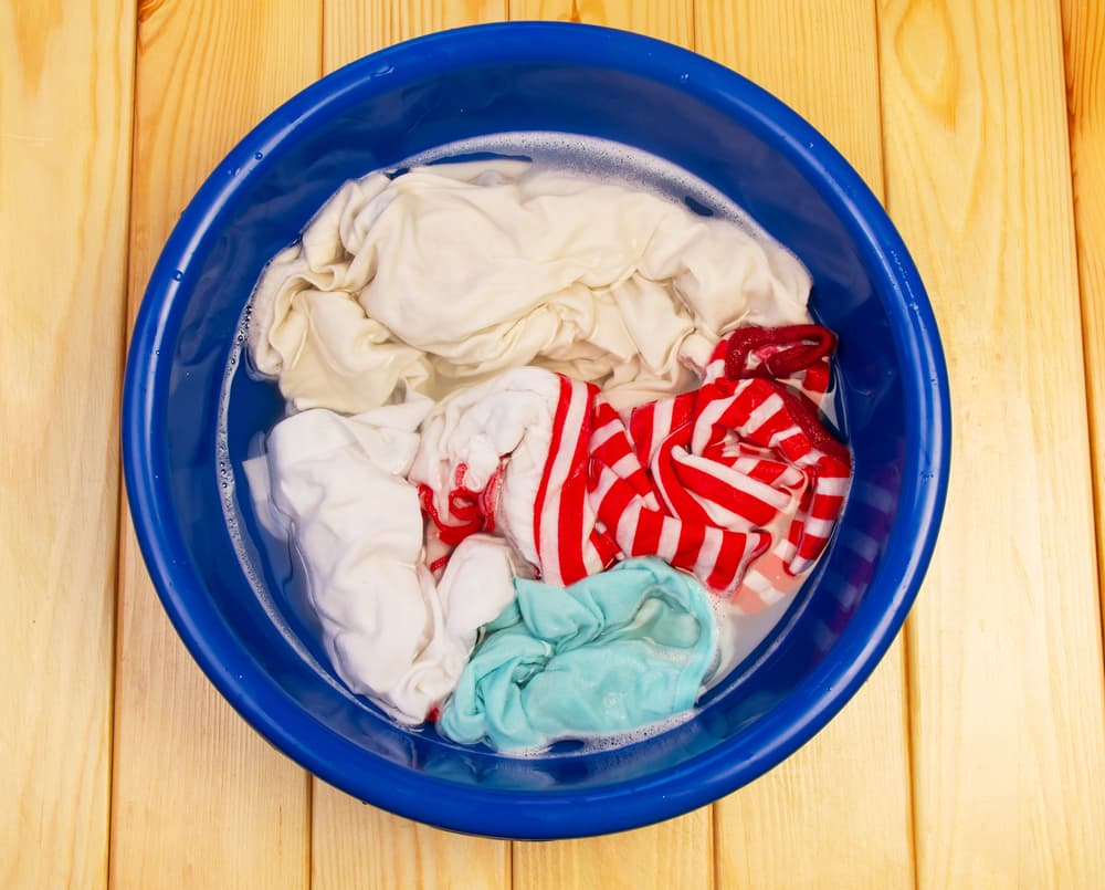 バケツに洗濯物を浸け込んでいる