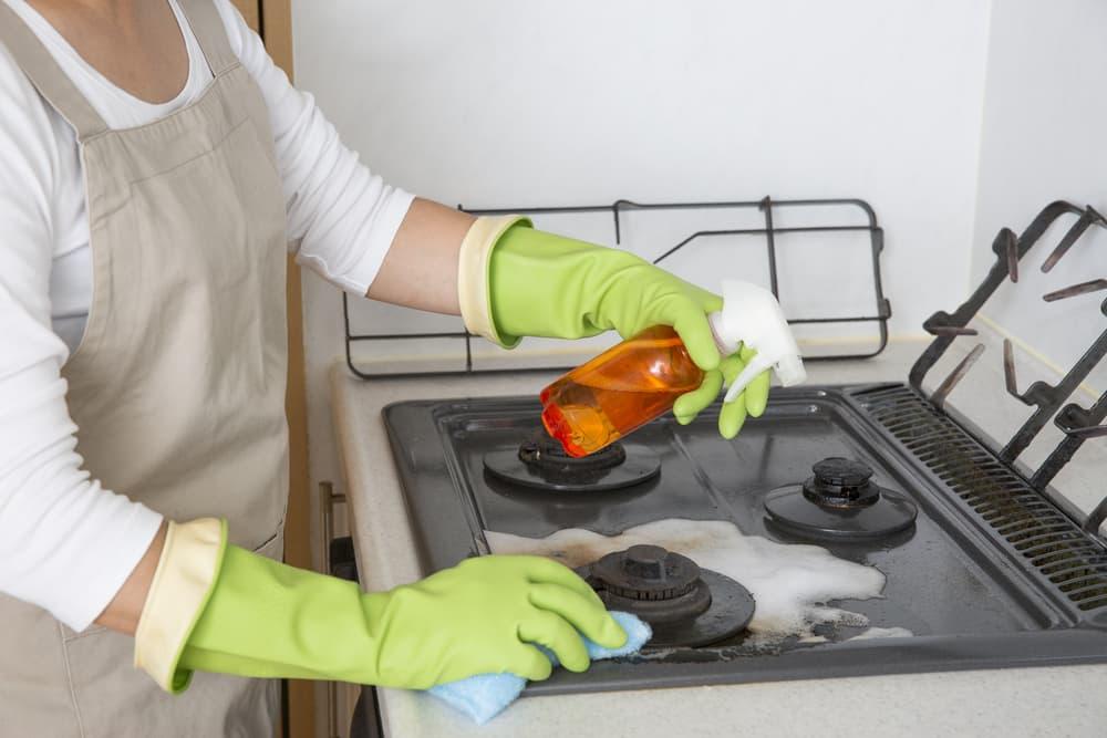 スプレーを使ってガスコンロを掃除している