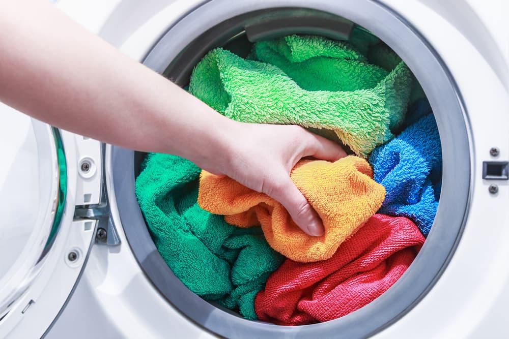 洗濯機にタオルを入れている女性の手元