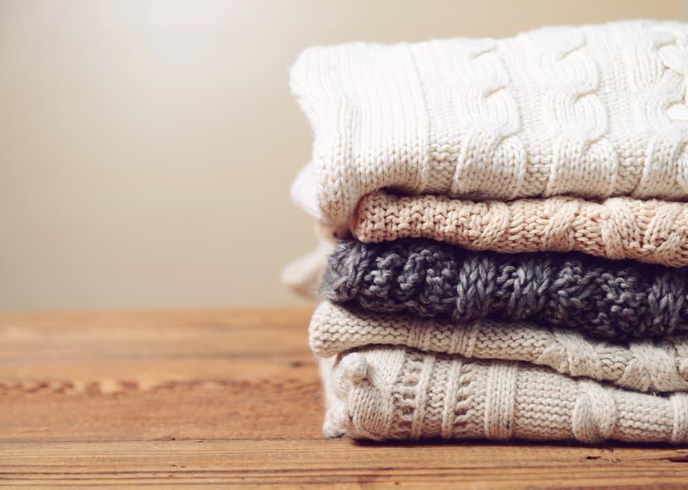 白やグレーなどのセーターが畳んで置いてある