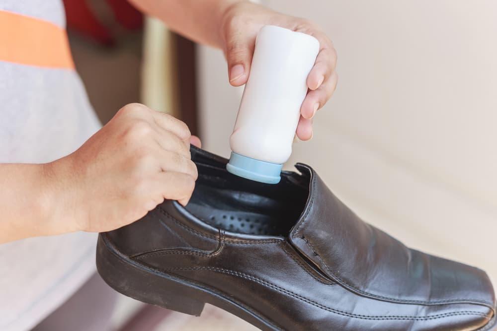 靴の中に白い入れ物の中身を振りかけている
