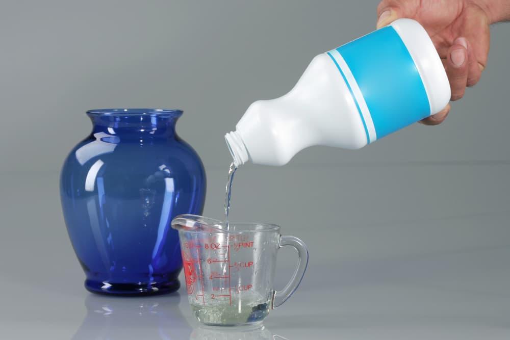 計量カップに液体洗剤を入れている