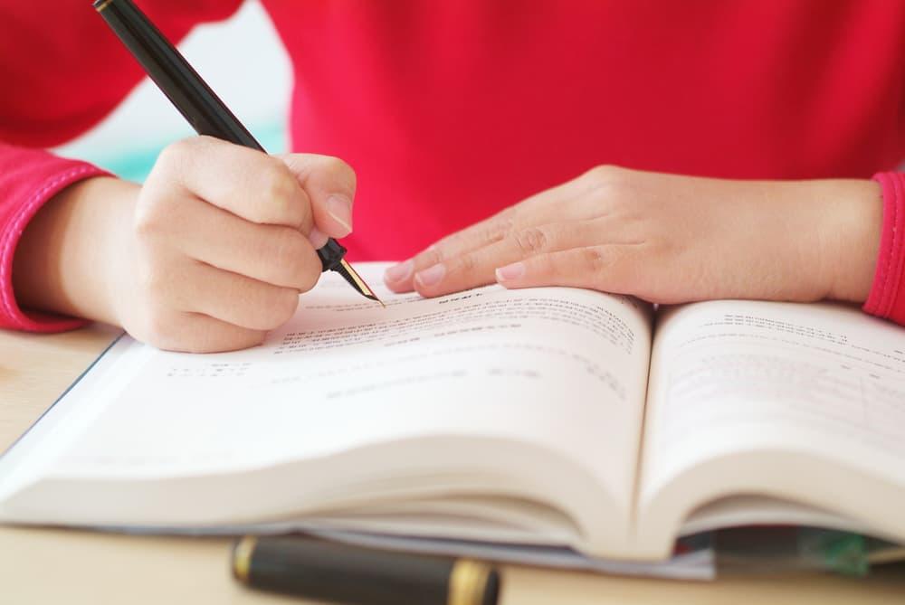 ボールペンでノートに書き込む手元