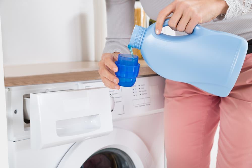 洗剤を計量カップに入れている女性