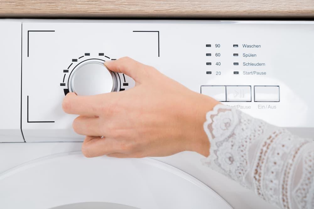 洗濯機のタイマーを設定している