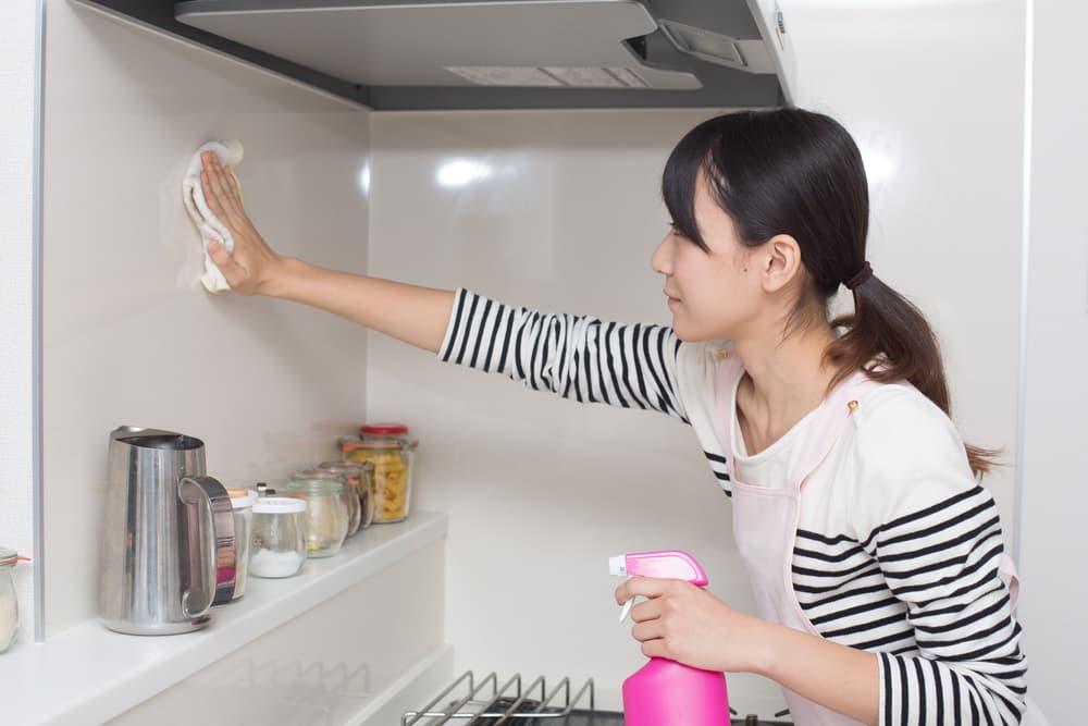 キッチンの壁を拭いている