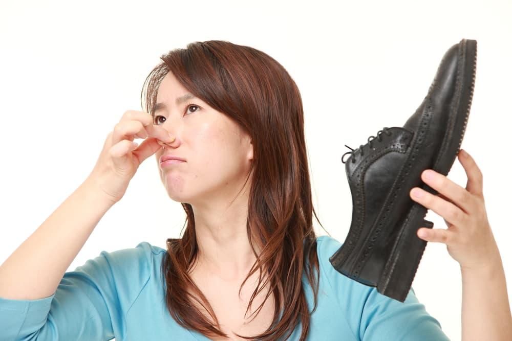 女性が靴を片手に鼻を押さえている