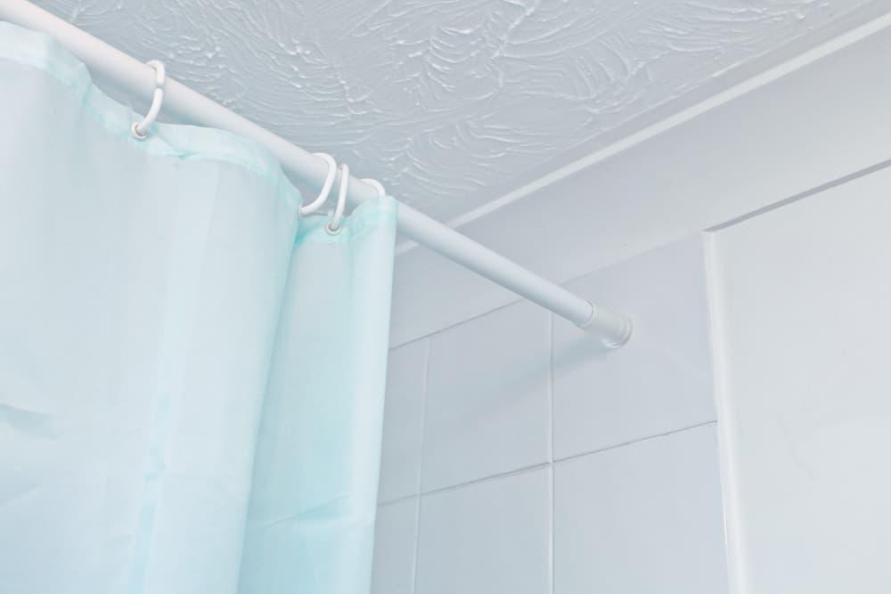 白い壁と水色のシャワーカーテン