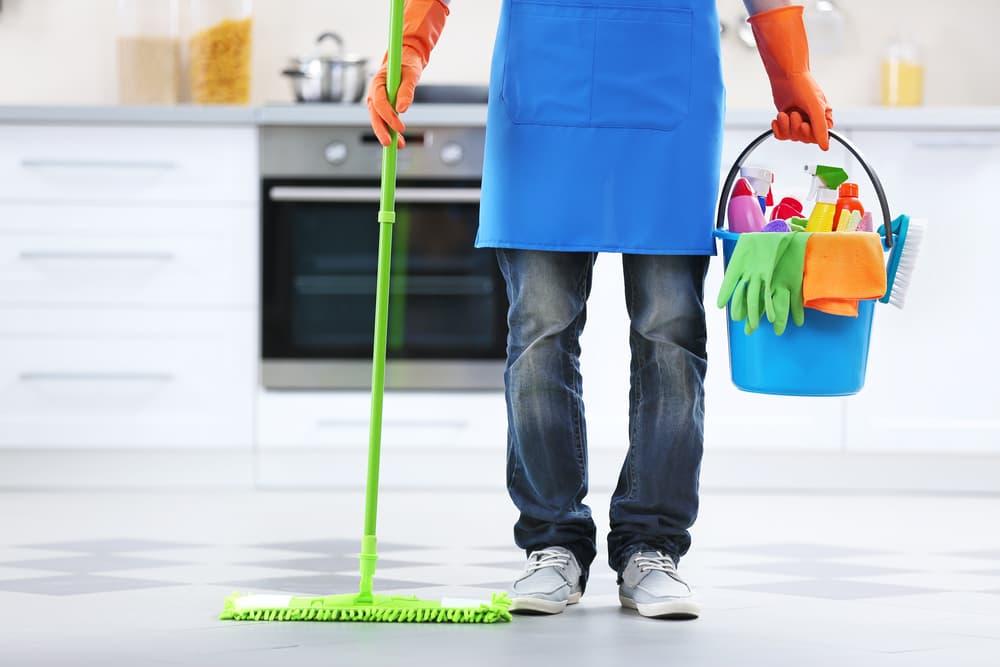 掃除道具を持ったエプロン姿の人