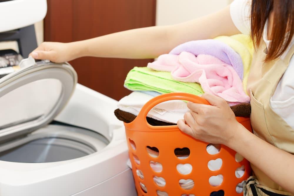 洗濯カゴを持ちながら洗濯機の蓋を開ける女性