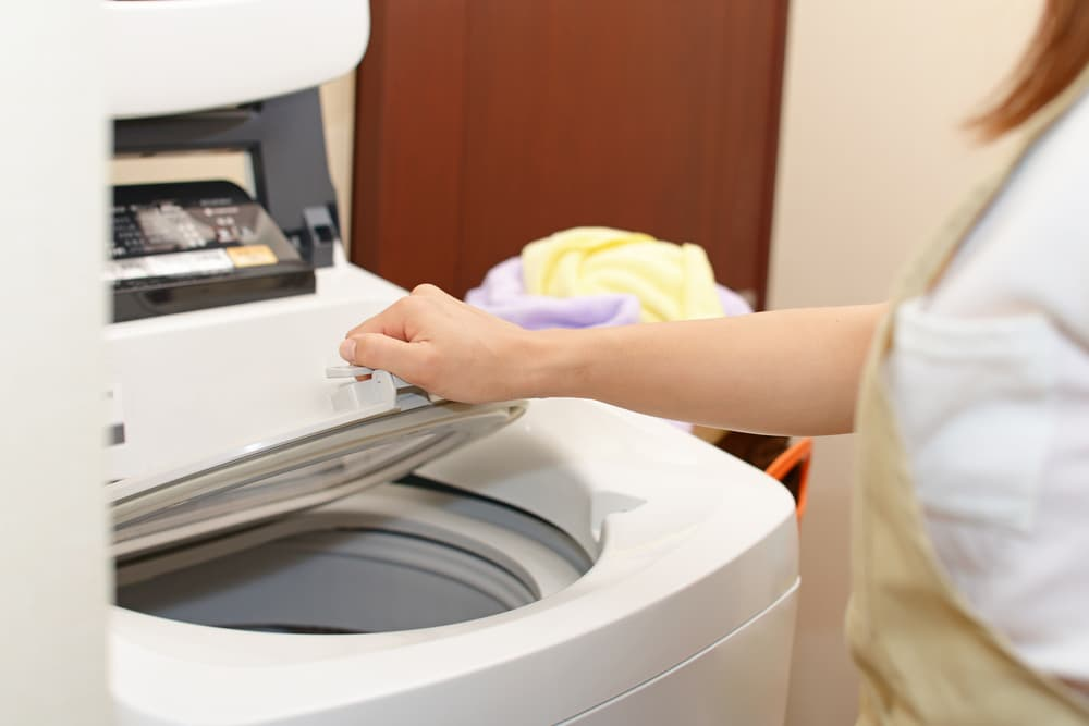 洗濯機の蓋を開ける女性の手元