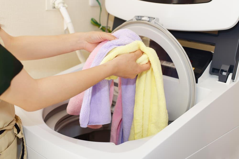洗濯機にタオルを入れようとしている
