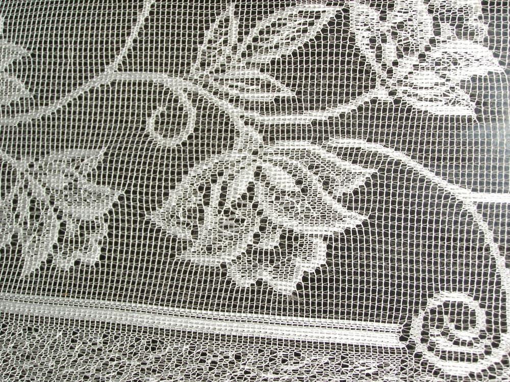 白の花柄のレースカーテンのアップ